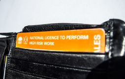 Krajowa koncesja wykonywać wysokiego ryzyka pracy kartę w czarnym portflu fotografia stock