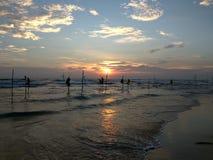 Krajowi połowów mieszkanowie patrzeje fala które siedzą na słupach blisko brzeg wieczór ocean indyjski Sri Lanka, barwili Fotografia Stock