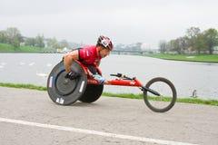 KRAKÓW, POLONIA - 28 DE ABRIL: Corredores de maratón del hombre de Cracovia Marathon.Handicapped en una silla de ruedas en las cal Imagen de archivo libre de regalías