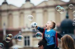 KRAKÓW, POLONIA - 27 DE JUNIO DE 2015: Muchacho que se sienta en los hombros y las burbujas gigantes tocadas del papá fotos de archivo libres de regalías