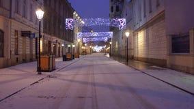 KRAKÓW, POLONIA - ENERO, 14, 2017 iluminó la calle vacía de la ciudad vieja en la nieve Imagenes de archivo