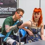 KRAKÓW, POLONIA - la gente hace tatuajes en el 10mo convenio internacional del tatuaje en el centro de la Congreso-EXPO Imágenes de archivo libres de regalías