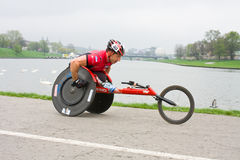 KRAKAU, POLEN - 28. APRIL: Mann-Marathonläufer Cracovia Marathon.Handicapped in einem Rollstuhl auf den Stadtstraßen Lizenzfreies Stockbild