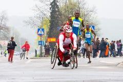 KRAKAU, POLEN - 28. APRIL: Mann-Marathonläufer Cracovia Marathon.Handicapped in einem Rollstuhl auf den Stadtstraßen Lizenzfreie Stockfotos
