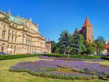 Krakau-Stadt - Kirche, Theater, purpurrote Blumen lizenzfreies stockbild