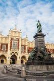Krakau - Statue von Adam Mickiewicz und von Sukiennice, die mit Rathaus im Hintergrund buidning sind Lizenzfreies Stockfoto