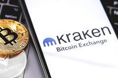 Kraken logo of exchange on the screen smartphone