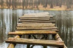 Krakingowy drewniany footbridge nad woda Zdjęcia Stock
