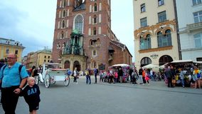 Krakow city center, Poland. KRAKOW, POLAND - JUNE 13, 2018: The horse-drawn carriages ride along the crowded Plac Mariacki square with a view on St Mary`s stock video footage