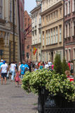 Krakow, The Kanoniczna street. Krakow, Poland - June 12, 2015: In the foreground the beautiful flowers at the garden restaurant. In the background a view of the Stock Images