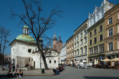 Krakow Old Town Square. The Church of St. Wojciech in the Old Town Krakow streets filled with tourists, horse and carriage restaurants on the sidewalk Royalty Free Stock Image