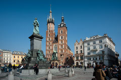Krakow Old Town Square. The Church Kościół Mariacki in the Old Town Krakow streets filled with tourists, with the bronze statue of Adam Mickiewicz in the Stock Photography