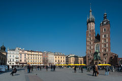 Krakow Old Town Square. The Church Kościół Mariacki in the Old Town Krakow streets filled with tourists, with cafe's restaurants and bars lining the square Stock Photography