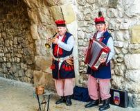 Krakow, Polônia - 19 de novembro de 2017: Os músicos na roupa polonesa tradicional executam para turistas em uma maneira autêntic Imagem de Stock