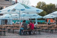 KRAKOW, POLÔNIA, o 21 de abril de 2018, muitos povos senta-se no portab de madeira fotografia de stock royalty free
