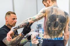 KRAKOW, POLÔNIA - os povos fazem tatuagens na 10o convenção internacional da tatuagem no centro da Congresso-EXPO Fotografia de Stock Royalty Free
