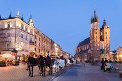 krakow poland Aftonsikt med den Mariacki kyrkan Arkivfoton