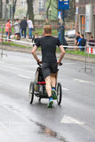 KRAKOW, POLAND - APRIL 28 : Cracovia Marathon. Wladyslaw Wachulec with his son in a wheelchair on the city streets Royalty Free Stock Photo