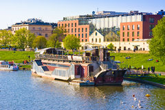 KRAKOW, POLAND - APRIL 25, 2015: Restaurant boat on VIstula river with Hilton hotel, Poland. Luxurious property with glass-covered Stock Photography