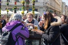 KRAKOW, POLAND, April 2, 2018, Three old women eat street food a royalty free stock photo
