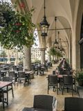 Sukiennice arcades with outdoors restaurant. KRAKOW, POLAND - AUGUST 07 2017: Sukiennice arcades with outdoors restaurant tables and chairs, Main Market Square Royalty Free Stock Images