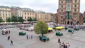 Undefined people in Krakow city - Poland. KRAKOW, POLAND - AUGUST 3, 2017: undefined people walking on the Market Square Rynek Glowny It is a biggest square stock video