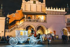 Horse-drawn carriage before the Sukiennice on The Main Market Square in Krakow, night view, Po. Krakow, Poland - December 15, 2017: Horse-drawn carriage before Royalty Free Stock Images