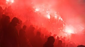 A Polish Derby. KRAKOW, POLAND-DECEMBER 13, 2017: Polish soccer fans lighting smoke flares at Cracovia Stadium, during the Polish Premiere League match Cracovia Stock Photos