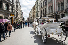 KRAKOW, POLAND 10.05.2015 Horse carriages at main square on a summer day Stock Photo