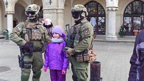 KRAKOW, POLAND - JANUARY, 14, 2017 Armed special force soldiers posing with civilians with Polish and American flags at. KRAKOW, POLAND - JANUARY, 14, 2017 Armed stock footage