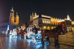 Horse-drawn Carriage before the Sukiennice on The Main Market Square in Krakow, night view, Pol. Krakow, Poland - January 22, 2017: Horse-drawn Carriage before Stock Photos