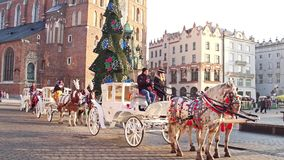 KRAKOW, POLAND - JANUARY, 14, 2017 Retro horse drawn carriages and Christmas decorated touristic Old town street Stock Photo
