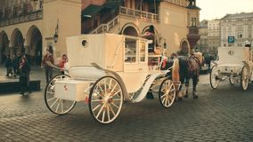 KRAKOW, POLAND - JANUARY, 14, 2017 Steadicam shot of retro horse drawn carriages and Christmas decorated Old town street stock video footage