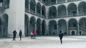 KRAKOW, POLAND - JANUARY, 14, 2017 Tourists making photos at inner courtyard of Wawel Castle. Local landmark and popular Royalty Free Stock Photos