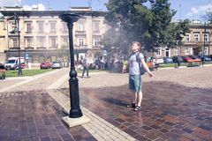 Krakow, Poland, July 28, 2018, A young guy standing under a street water sprayer and enjoying the coolness escaping from royalty free stock photos