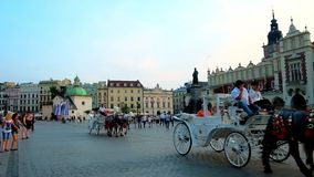 The evening Market Square with crowds of tourists, Krakow, Poland. Krakow, Poland - June 11, 2018: The evening Market Square with crowds of tourists, riding stock video footage