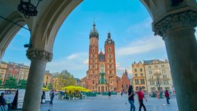 St Mary`s Basilica in Krakow, Poland. KRAKOW, POLAND - JUNE 12, 2018: The Gothic bell towers of St Mary`s Basilica are seen through the arcade of Cloth Hall stock video footage