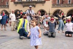 Krakow, Poland, June 01, 2018, Little girl standing among a crow stock photo