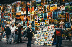 KRAKOW, POLAND - JUNE 27, 2015: Paintings for sale hang on a wall in Krakow. Stock Images