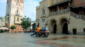 The street sweeper vehicle washes central square in Krakow, Poland. KRAKOW, POLAND - JUNE 11, 2018: The street sweeper vehicle washes area at the entrance to the stock video footage