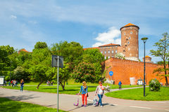 KRAKOW, POLAND - JUNE 08, 2016: Tourists walking near historical complex of Royal Wawel Castle with well seen Sandomierska tower o Stock Images