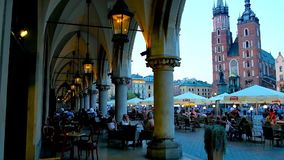 The outdoor cafe in Main Market Square in Krakow, Poland. KRAKOW, POLAND - JUNE 11, 2018: The view from the arcade of the Cloth Hall Sukiennice on crowded stock footage