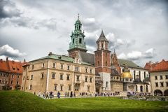 Krakow, Poland - June 04, 2017: Wawel cathedral with chapels on green hill. Tourists at catholic church on cloudy sky. Architectur. E and design. Travelling Stock Images