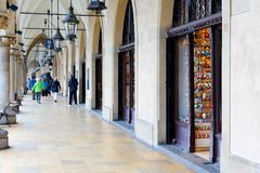 People walk under arcades in Krakow Stock Images
