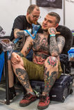 KRAKOW, POLAND - People make a tattoos at the 10-th International Tattoo Convention in the Congress-EXPO Center. KRAKOW, POLAND - JUNE 6, 2015: People make a stock photo