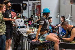 KRAKOW, POLAND - People make a tattoos at the 10-th International Tattoo Convention in the Congress-EXPO Center. KRAKOW, POLAND - JUNE 6, 2015: People make a royalty free stock photography