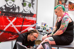 KRAKOW, POLAND - People make a tattoos at the 10-th International Tattoo Convention in the Congress-EXPO Center. KRAKOW, POLAND - JUNE 6, 2015: People make a stock images