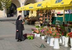 Nun and flowers, Krakow, Poland. KRAKOW, POLAND - SEPTEMBER 11, 2017: Elderly nun looks onto fresh flowers at Main Square of Old Town, Krakow Royalty Free Stock Photos