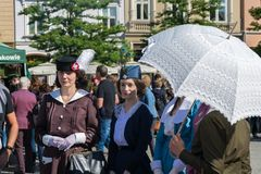 Krakow, Poland - September 23, 2018: nStylish young women dressed in World War I period clothing walk among tourists at stock photo