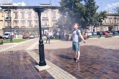 Krakow Polen, Juli 28, 2018, ungt grabbanseende för A under en stre royaltyfria foton